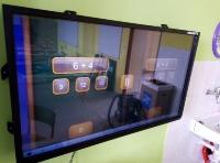 Dotyková televize na zeď. Pevná instalace s držákem upevněným do zdi.